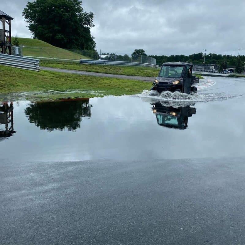 Gator driving thru lake on track
